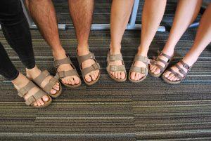 A group of feet wearing Birkenstock's.