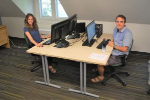 A man and a woman sitting at their computers.