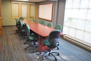 A sunny, carpeted conference room with green and blue walls.