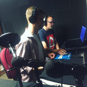 Two men recording a podcast in a basement with microphones, headphones, and a computer.